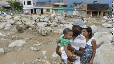 A man holds his son as he stands amid the remains of Mocoa, Putumayo on April 2 after deadly mudslides.