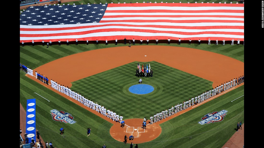 Teams line up for the national anthem before the Opening Day game in Los Angeles on Monday, April 3.