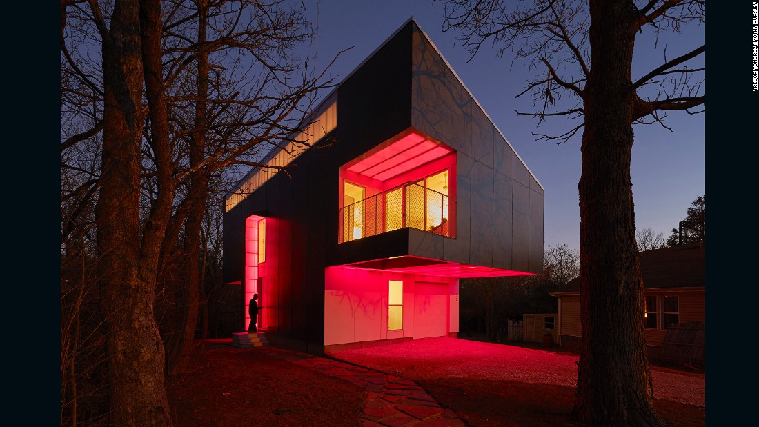 The house, surrounded by nature, projects colorful LED lights that the architect and his family choose at night.
