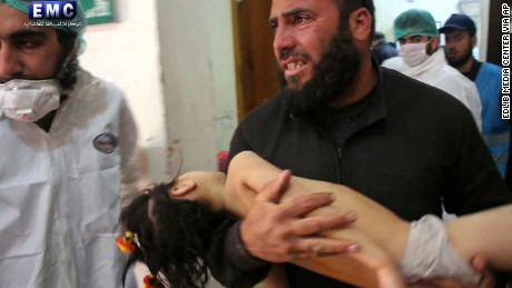 A man carries a child into a makeshift hospital after Tuesday's attack in Idlib province.