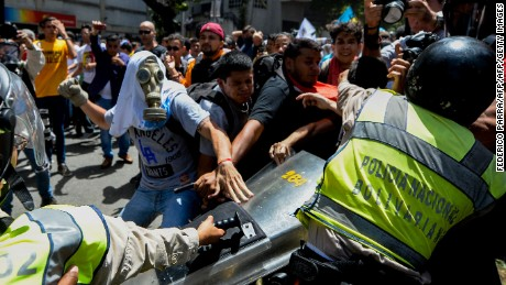 Opposition activists scuffle with riot police during a protest against President Nicolas Maduro's government in Caracas on April 4, 2017.  Activists clashed with police in Venezuela Tuesday as the opposition mobilized against moves to tighten President Nicolas Maduro's grip on power. Protesters hurled stones at riot police who fired tear gas as they blocked the demonstrators from advancing through central Caracas, where pro-government activists were also planning to march. / AFP PHOTO / FEDERICO PARRA        (Photo credit should read FEDERICO PARRA/AFP/Getty Images)