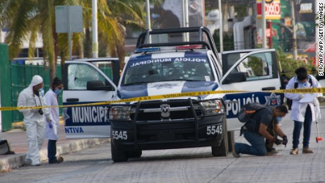 Forensic personnel and investigators collect evidence of an attack against a municipal police patrol car in Cancun, Quintana Roo state, Mexico on March 14, 2017.  According to preliminary reports an indeterminate number of policemen were wounded in the attack carried out by gunmen on a motorcycle.  / AFP PHOTO / STR        (Photo credit should read STR/AFP/Getty Images)