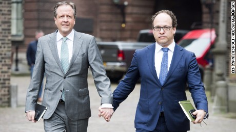 Alexander Pechtold (L) and Wouter Koolmees of the D66 party arrive for a political meeting, holding hands in solidarity with a gay couple.