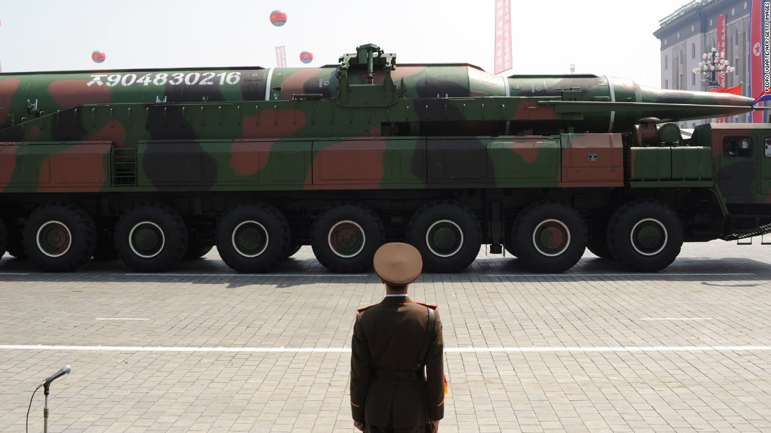 A North Korean soldier stands guard in front of a military vehicle carrying what is believed to be a Taepodong-class missile during a military parade to mark the 100th birthday of the country's founder Kim Il Sung in Pyongyang