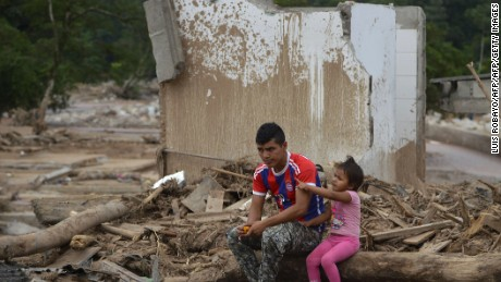 "A man and his daughter remain amid rubble in Mocoa, Putumayo department, Colombia on April 4, 2017.  Meanwhile, looting has become a problem in some areas. Local officials urged the government to dispatch more police and troops to secure the region and prevent the looting of abandoned homes. ""What the mudslides didn't carry away, the thieves did,"" one survivor of the disaster, Juan Luis Hernandez, 33, told AFP in the devastated San Miguel neighborhood of Mocoa. / AFP PHOTO / LUIS ROBAYO        (Photo credit should read LUIS ROBAYO/AFP/Getty Images)"