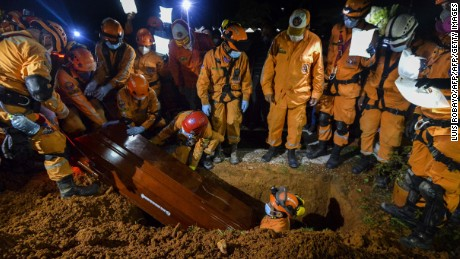 Colombian civil defense workers bury the coffin of their coworker Jesus Diago, 33, who died rescuing his family during a mudslide caused by heavy rains, at his funeral in the cemetery in Mocoa, Putumayo department, southern Colombia on April 4, 2017.  The Colombian government on Monday declared a state of economic emergency in the town of Mocoa in southern Colombia, after mudslides left more than 270 people dead, including 43 children. / AFP PHOTO / LUIS ROBAYO        (Photo credit should read LUIS ROBAYO/AFP/Getty Images)