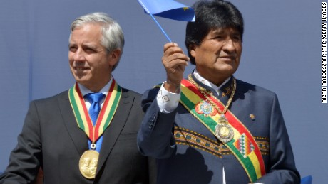 Bolivia's President Evo Morales Ayma (R) waves a maritime claim flag, next to Vicepresident Alvaro Garcia Linera, during the ceremony that marks the 138th anniversary of the Calama battle against Chile, where Bolivia lost its access to the sea, in La Paz on March 23, 2017. / AFP PHOTO / Aizar RALDES        (Photo credit should read AIZAR RALDES/AFP/Getty Images)
