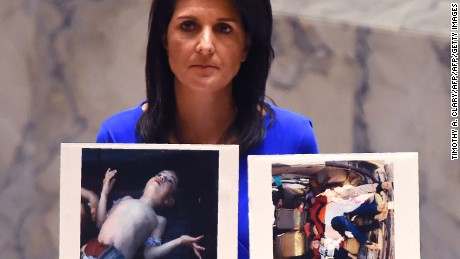 US Ambassador to the UN, Nikki Haley holds photos of victims as she speaks as the UN Security Council meets in an emergency session at the UN on April 5, 2017, about the suspected deadly chemical attack that killed civilians, including children, in Syria. / AFP PHOTO / TIMOTHY A. CLARY        (Photo credit should read TIMOTHY A. CLARY/AFP/Getty Images)