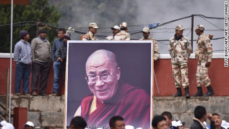 Indian security personnel stand being a poster of exiled Tibetan spiritual leader the Dalai Lama as he delivers religious teachings at the Buddha Stadium in Bomdila in India's north-eastern state of Arunachal Pradesh state on April 5, 2017. The Dalai Lama is visiting the northeast Indian state of Arunachal Pradesh, where he first crossed into the country, and where he is scheduled to hold a series of teachings. / AFP PHOTO / Biju BORO        (Photo credit should read BIJU BORO/AFP/Getty Images)