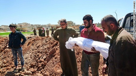 Syrians bury the bodies of victims of this week's chemical attack.