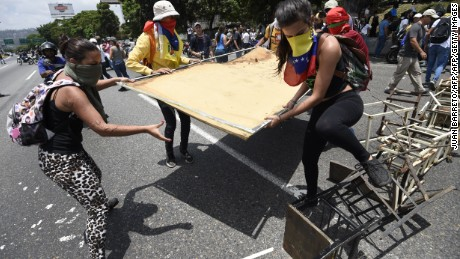 Venezuelan opposition activists set up a barricade during a protest against the government of President Nicolas Maduro on April 6, 2017 in Caracas. The center-right opposition vowed fresh street protests -after earlier unrest left dozens of people injured - to increase pressure on Maduro, whom they blame for the country's economic crisis. / AFP PHOTO / JUAN BARRETO        (Photo credit should read JUAN BARRETO/AFP/Getty Images)