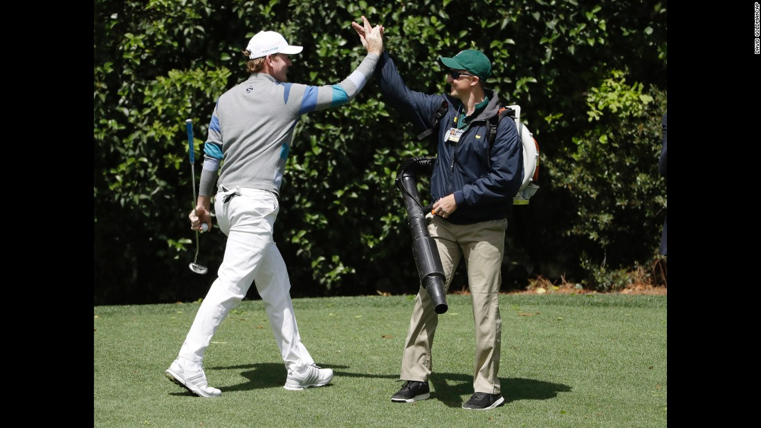 Brandt Snedeker, left, high-fives a crew member after making a putt on the fourth hole.