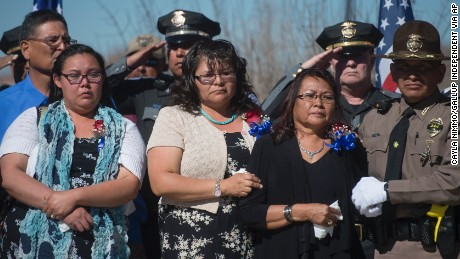 Largo's mother, Maggie Charley, right, is surrounded by friends and police at the memorial service.