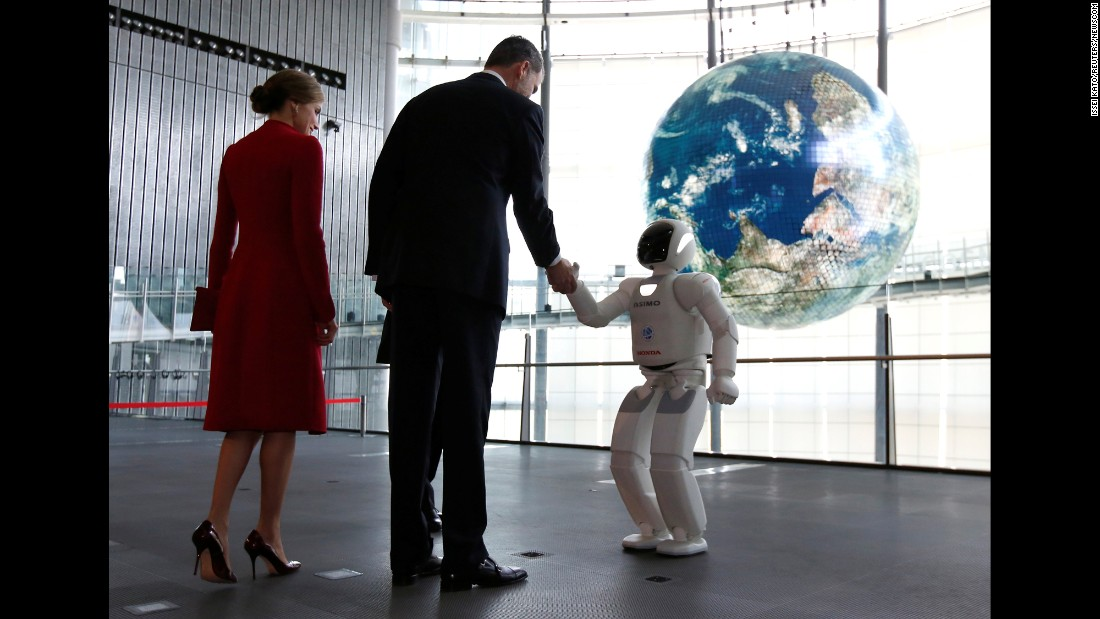Spain's King Felipe, accompanied by Queen Letizia, shakes hands with Honda Motor's humanoid robot Asimo as they visit the Miraikan museum in Tokyo on Wednesday, April 5.