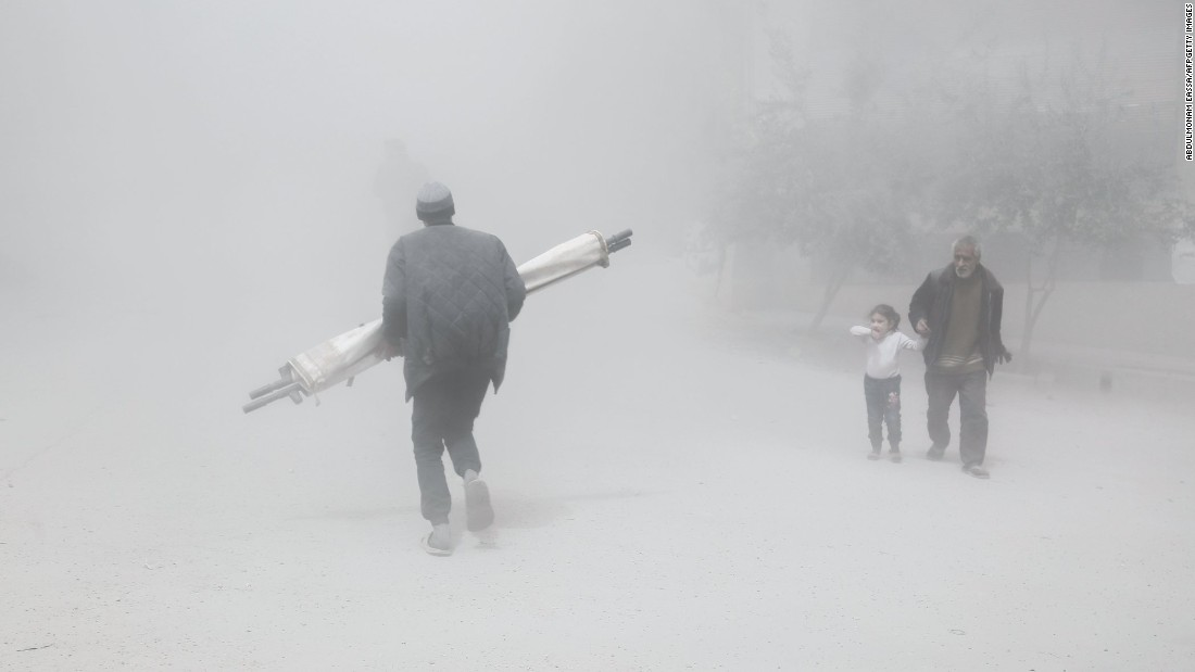A man and girl walk past a man carrying a folded stretcher after a reported airstrike in Hamouria, Syria, on Tuesday, April 4.