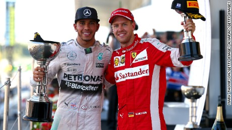 SUZUKA, JAPAN - SEPTEMBER 27:  Lewis Hamilton of Great Britain and Mercedes GP celebrates on the podium next to Sebastian Vettel of Germany and Ferrari after winning the Formula One Grand Prix of Japan at Suzuka Circuit on September 27, 2015 in Suzuka, Japan.  (Photo by Mark Thompson/Getty Images)