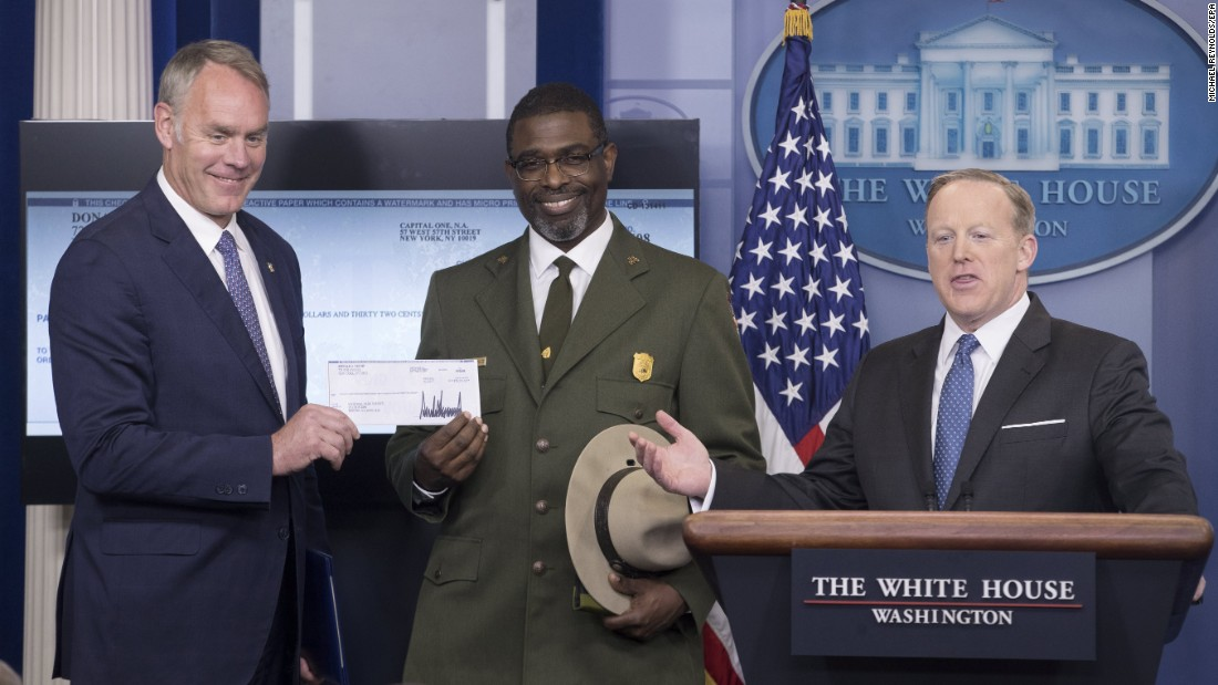 "White House Press Secretary Sean Spicer gestures after handing over a check Monday, April 3, to Interior Secretary Ryan Zinke, left, and Tyrone Brandyburg, the superintendent of the Harper's Ferry historical site. President Trump <a href=""http://money.cnn.com/2017/04/03/news/trump-salary-national-parks/"" target=""_blank"">donated the $78,333.32 salary he had earned so far</a> to the National Park Service -- ""every penny that the President received from the first quarter,"" Spicer told journalists. Trump is fulfilling a campaign pledge to donate his salary."