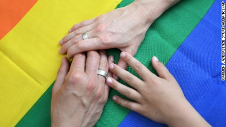 This photo illustration of a married lesbian couple together with their son's hands on a rainbow flag.