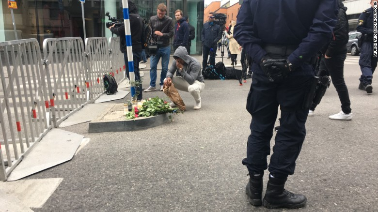 A man lays flowers Saturday by a cordon securing the scene of the truck attack in Stockholm.