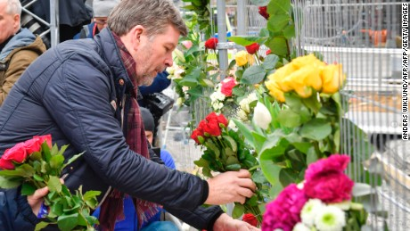 People lay flowers Saturday at the scene of a truck attack in central Stockholm.