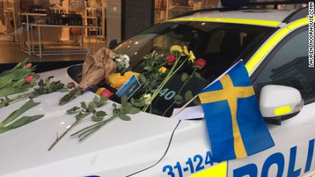 Cards and flowers have been left on police car windshields in the city center, thanking officers for their work.