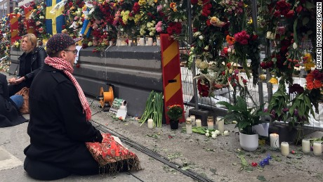 A mourner prays at the wall of flowers memorial that has sprung up down the street from the site of the Stockholm attack.