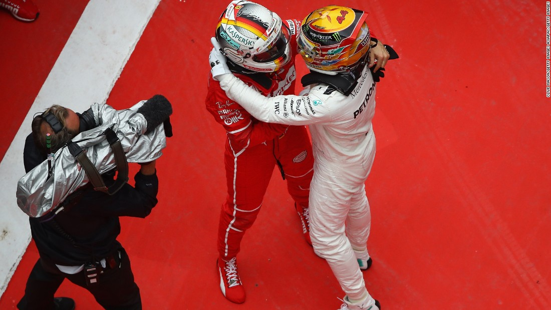 Race winner Hamilton (right) embraces Sebastian Vettel of Ferrari who finished second.