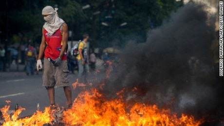 "Demonstrators protesting against President Nicolas Maduro's government and riot police clash in Caracas on April 8, 2017.  The opposition is accusing pro-Maduro Supreme Court judges of attempting an internal ""coup d'etat"" for attempting to take over the opposition-majority legislature's powers last week."