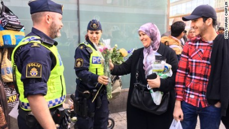 A woman in an Islamic headscarf hands flowers to police at a vigil Sunday after the Stockholm truck attack.