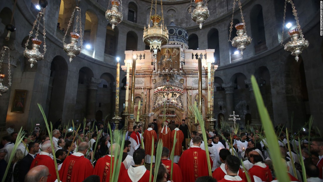 Catholic priests hold palm branches at the Church of the Holy Sepulchre in Jerusalem on Sunday, April 9.