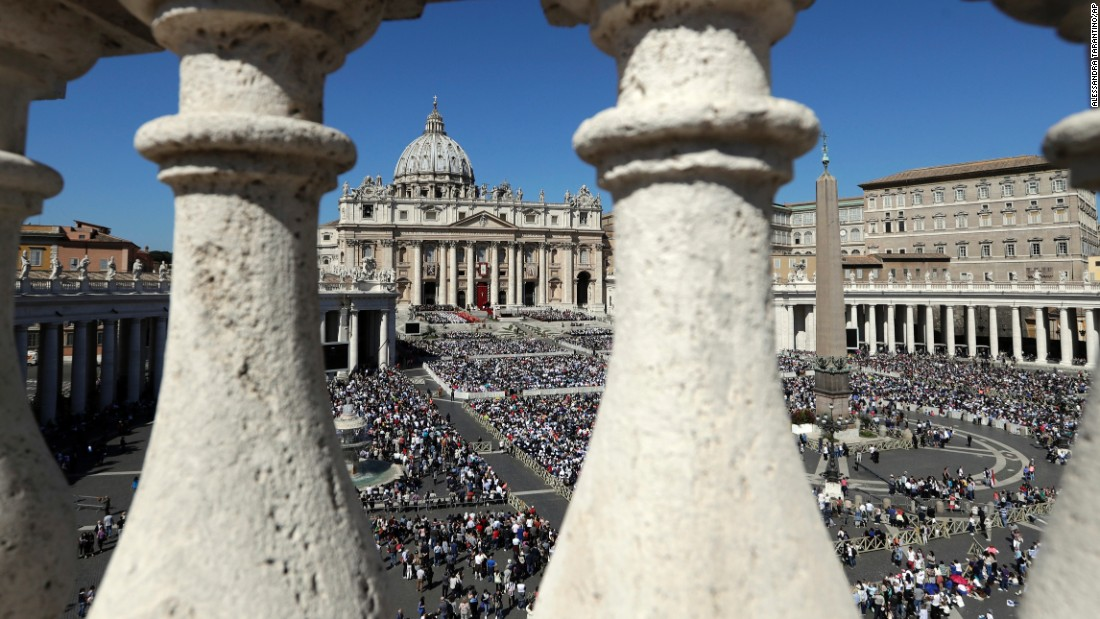 Faithful fill St. Peter's Square as Pope Francis celebrates a Palm Sunday Mass at the Vatican.