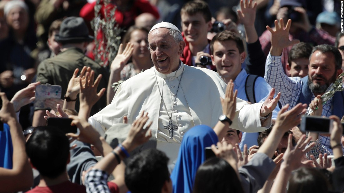 Pope Francis waves to the crowd at the Palm Sunday Mass.