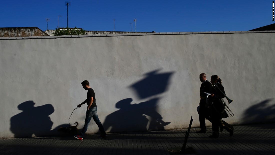 Musicians, right, walk to a church before a Holy Week procession in Cordoba, Spain, on April 9.