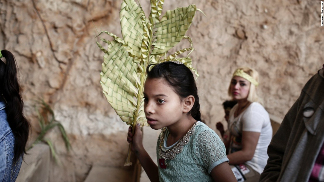 A girl holds a palm frond during a Palm Sunday Mass in Cairo.