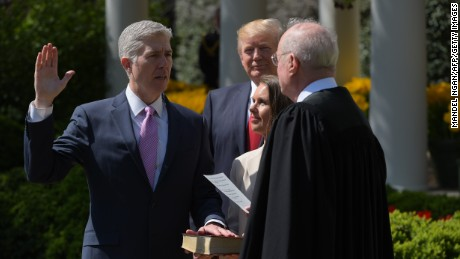 US President Donald Trump watches as Justice Anthony Kennedy(R) administers the oath of office to Neil Gorsuch as an associate justice of the US Supreme Court in the Rose Garden of the White House on April 10, 2017 in Washington, DC as Louise Gorsuch looks on.