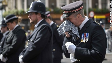 A policeman reacts during a broadcast of Palmer's funeral service from Southwark Cathedral.