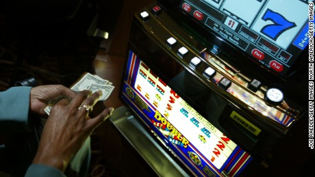 HOLLYWOOD, FL - MAY 11:  A gambler prepares to put her money in a slot machine May 11, 2004 during the grand opening for the Seminole Hard Rock Hotel and Casino in Hollywood, Florida. South Florida's Seminole Indian Tribe has opened the state's biggest casino complex. The hotel has 500 rooms, 4,000 video gaming machines, poker tables and several restaurants. The public area has large ballrooms and a six-acre pool site with a 180-foot water slide. The Seminoles have shown big profits in past years by selling tax-free cigarettes and operating bingo halls, but the Hard Rock is its biggest venture thus far.  (Photo by Joe Raedle/Getty Images)