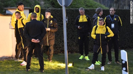 Head coach Thomas Tuchel, right, and players of Borussia Dortmund stand outside their team bus after it was damaged in an explosion.