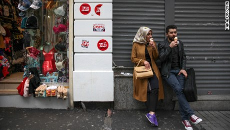 "A couple in Istanbul's city center on Sunday, April 9, perch on a street adorned with stickers that say ""Evet"" -- the symbol for the ""Yes"" campaign."