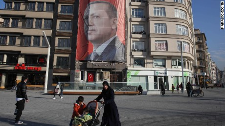 "Istanbul residents walk past Erdogan's ""Yes"" campaign banner in Istanbul's Taksim Square on Sunday."