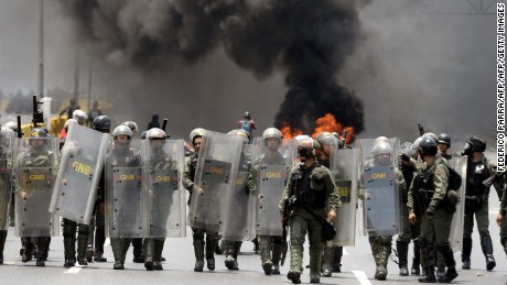 Riot police members take positions during clashes with demonstrators protesting against President Nicolas Maduro's government -for the fifth time in the last week- in Caracas on April 10, 2017. Venezuela's political crisis intensified last week when the Supreme Court issued rulings curbing the powers of the opposition-controlled legislature. The court reversed the rulings days later, but the opposition intensified its protests from that moment.  / AFP PHOTO / FEDERICO PARRA        (Photo credit should read FEDERICO PARRA/AFP/Getty Images)