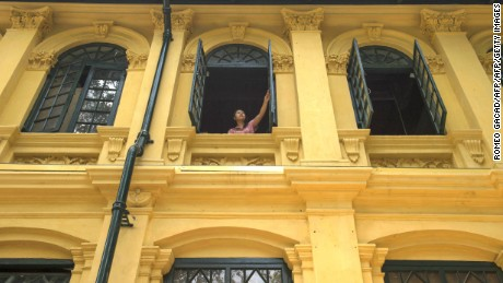 "A resident looks out from a window of a Yangon colonial building known by its address: ""491-501 Merchant Street."""
