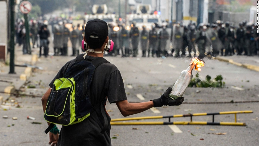 A Venezuelan opposition activist holds a lit Molotov cocktail during clashes with riot police.