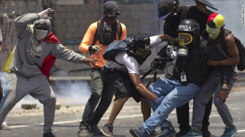 Demonstrators help a journalist whose leg was injured while covering clashes in Caracas on April 10.