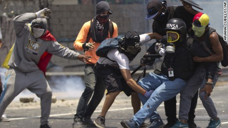 Demonstrators help a journalist who was injured in a leg while covering clashes between demonstrators and the  Bolivarian National Guard during a protest in Caracas, Venezuela, Monday, April 10, 2017. Opponents of President Nicolas Maduro protested on the streets of the capital as part of an ongoing protest movement that shows little sign of losing steam.