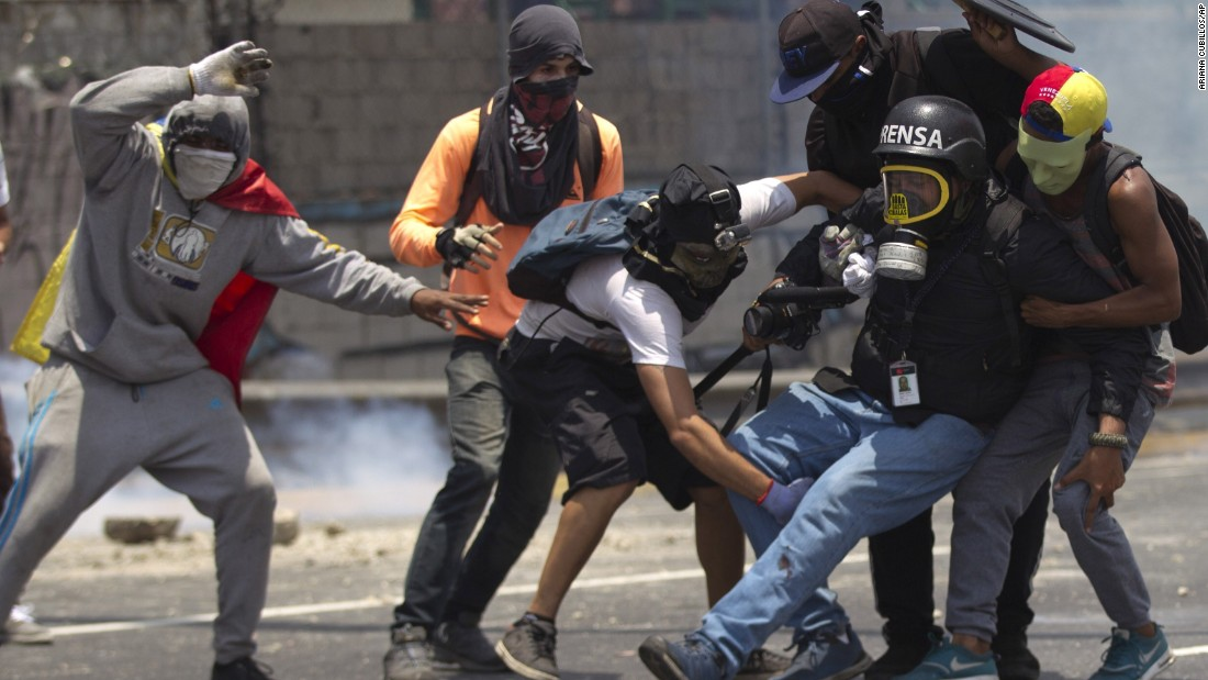 Demonstrators help a journalist whose leg was injured while covering clashes between demonstrators and the Bolivarian National Guard during a protest in Caracas, Venezuela.