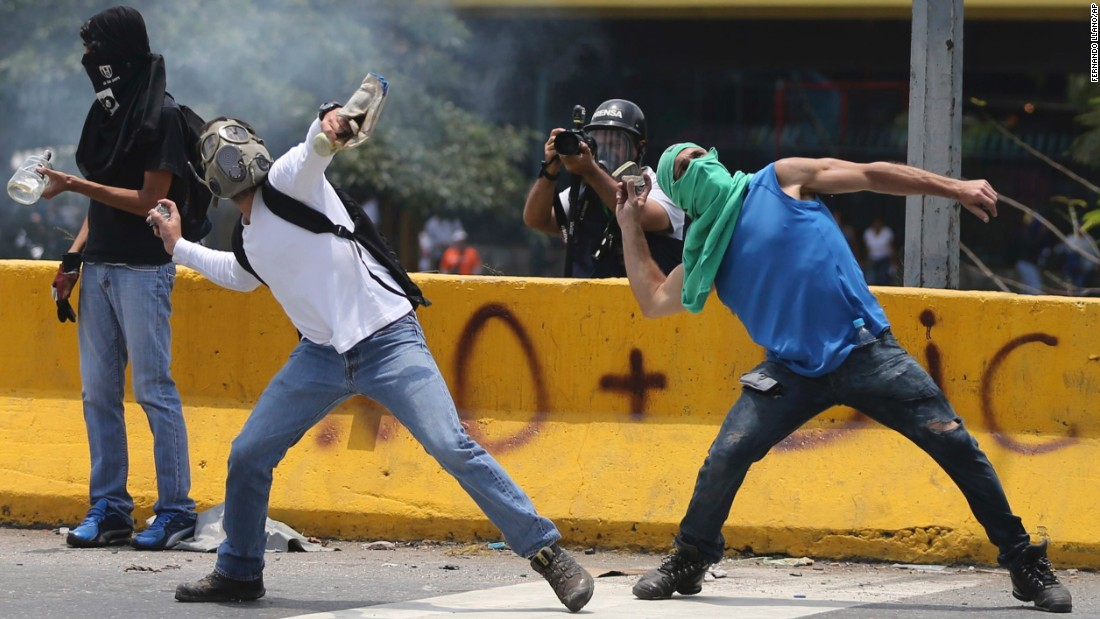 Demonstrators throw stones toward Venezuelan national guard troops during a protest in Caracas.