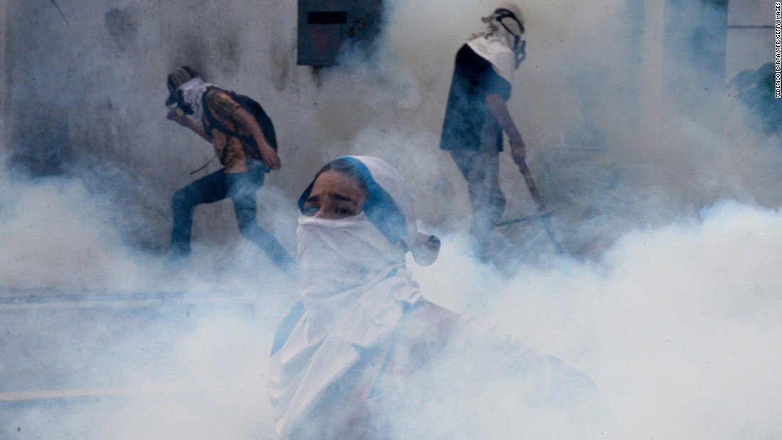 Opposition activists are engulfed by a cloud of tear gas in Caracas on April 10.
