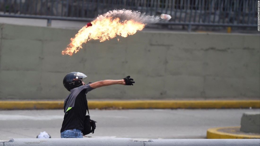 A demonstrator throws a Molotov cocktail during clashes with riot police in eastern Caracas.