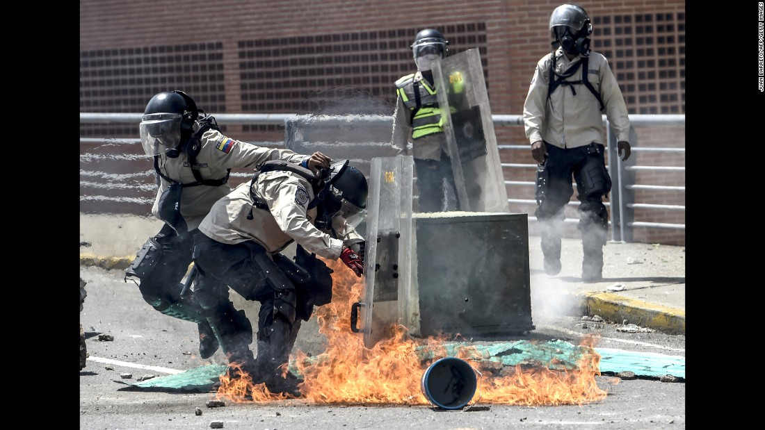 Riot police are attacked with Molotov cocktails.